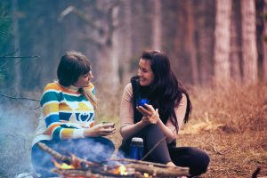 Conversation between two young adults in front of a campfire